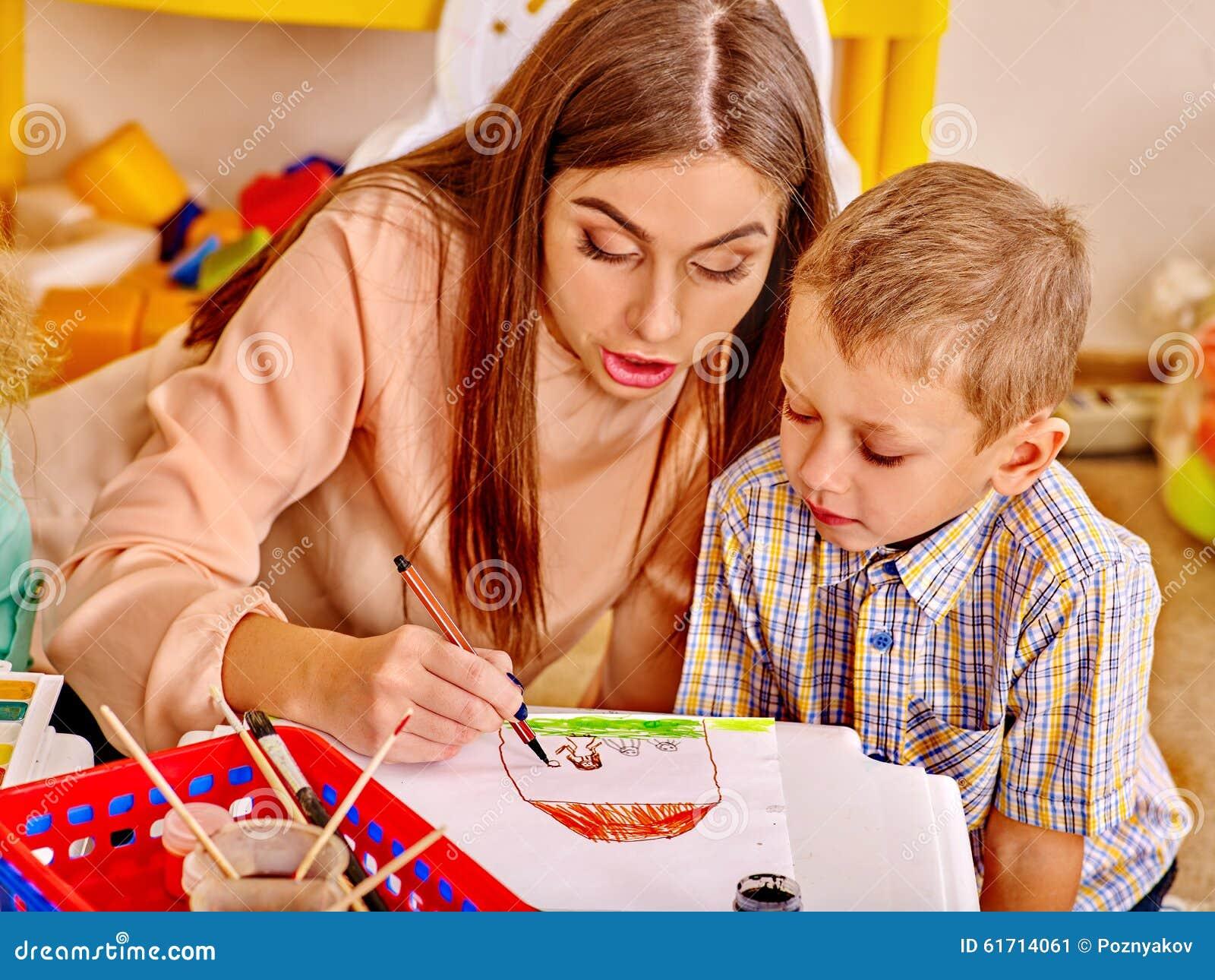 Kvinna med ungar som in rymmer färgat papper och lim