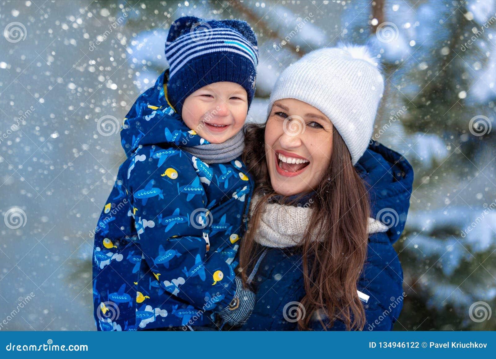 Kvinna och barn i vinter i natur lycklig stående för familj