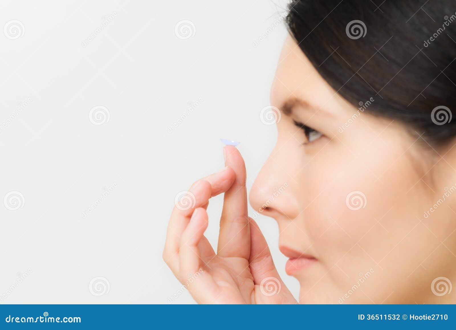 Kvinna omkring som förlägger en kontaktlins i hennes öga