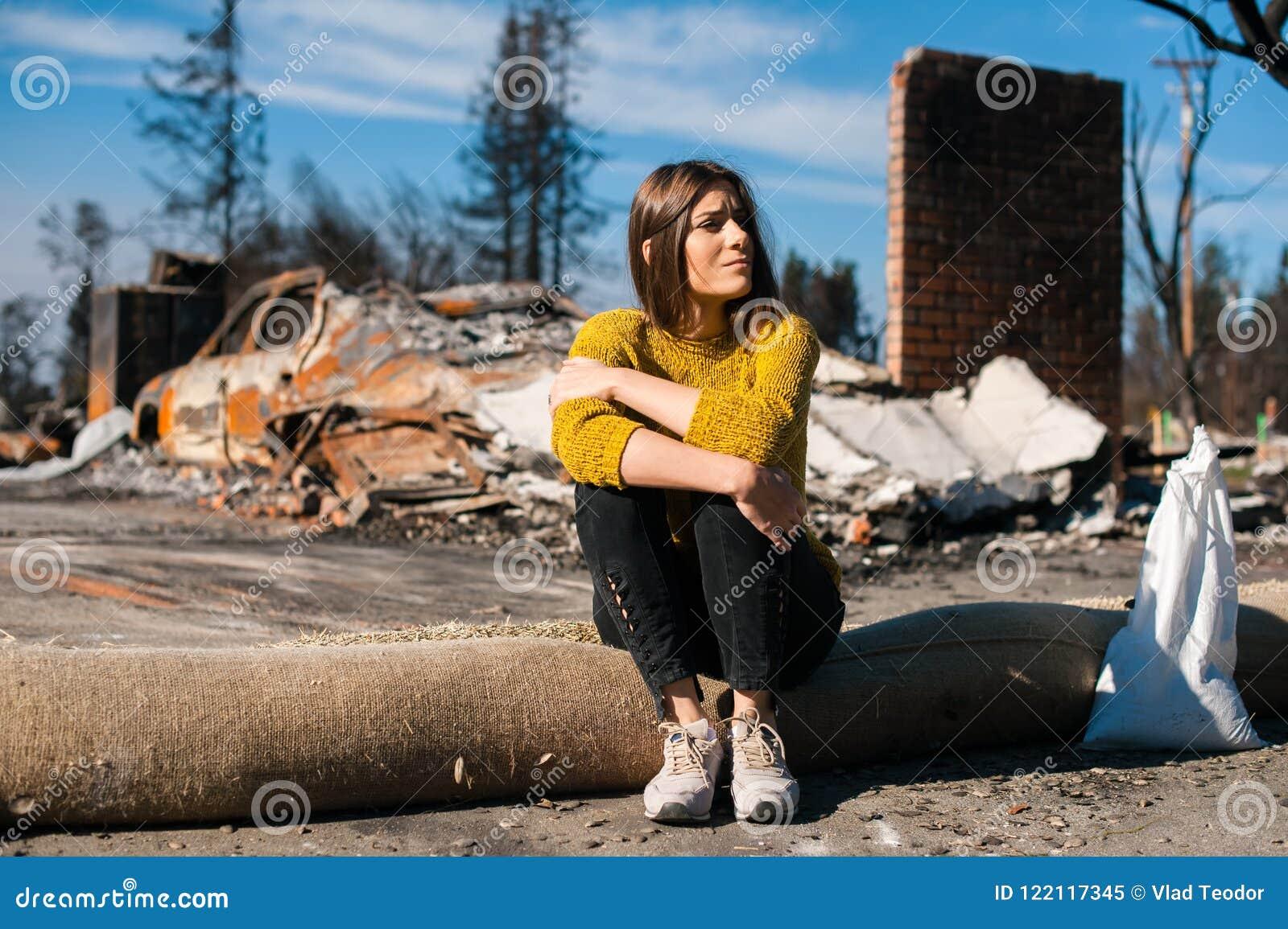 Kvinna på det brända förstörda huset och gården, efter brandkatastrof