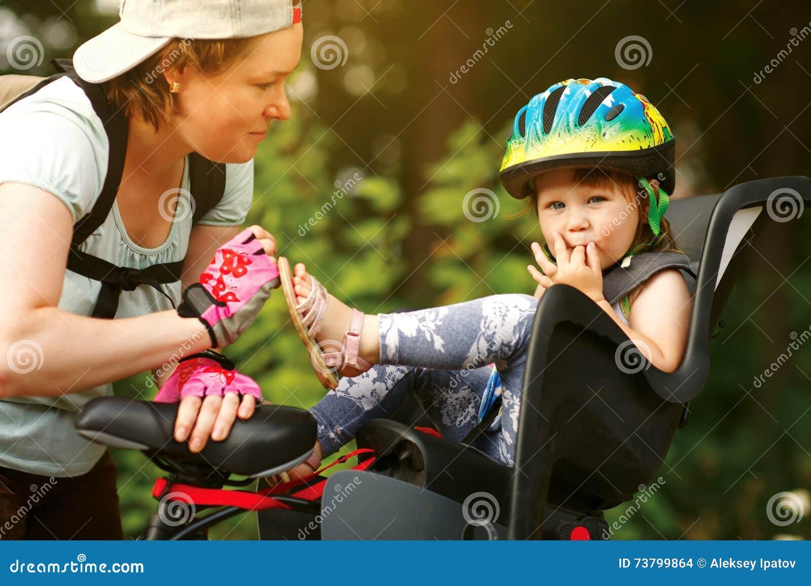 Kvinna på en cykel med den lilla dottern