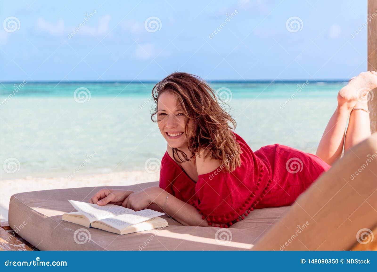 Kvinna på en sunchair som läser en bok i ett tropiskt läge Klart turkosvatten som bakgrund
