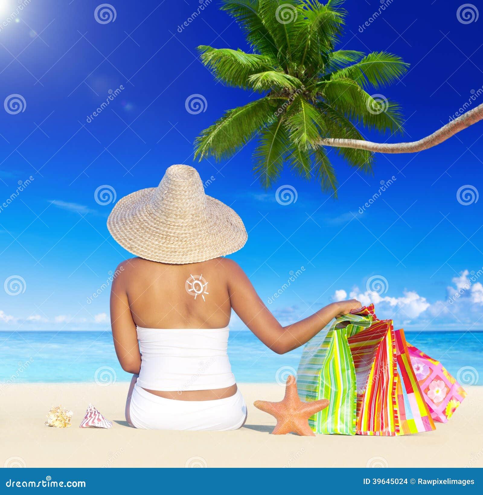Kvinna på ferie vid stranden med shoppingpåsar