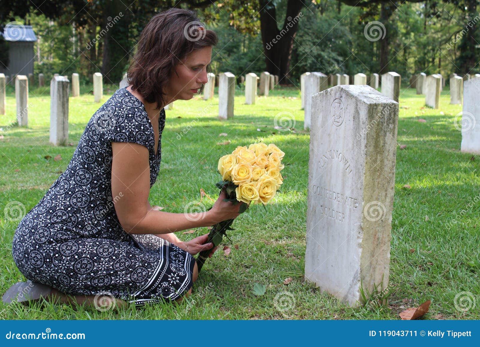 Kvinna på graven för ` s för okänd soldat med gula blommor