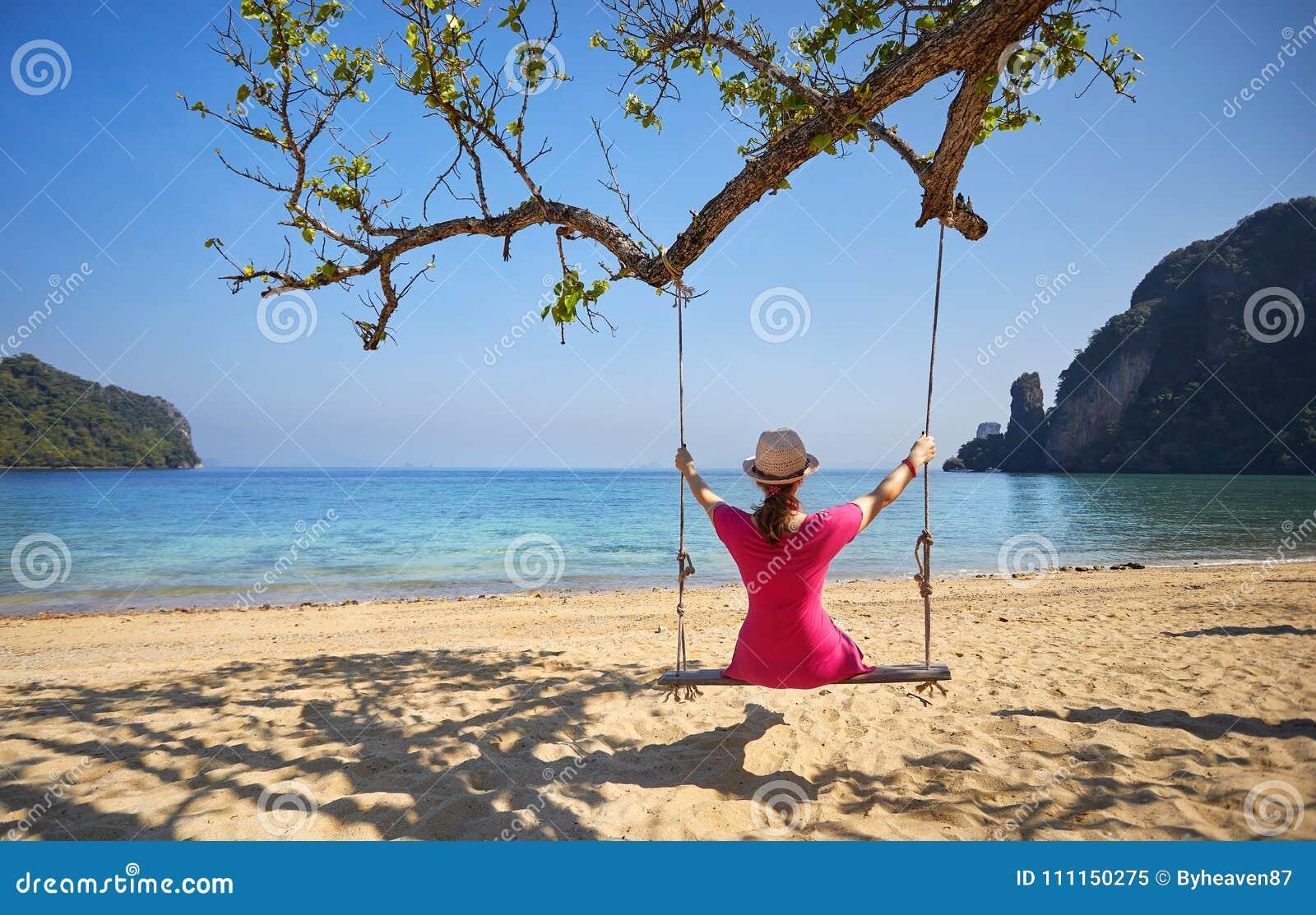 Kvinna på gunga på den tropiska ön