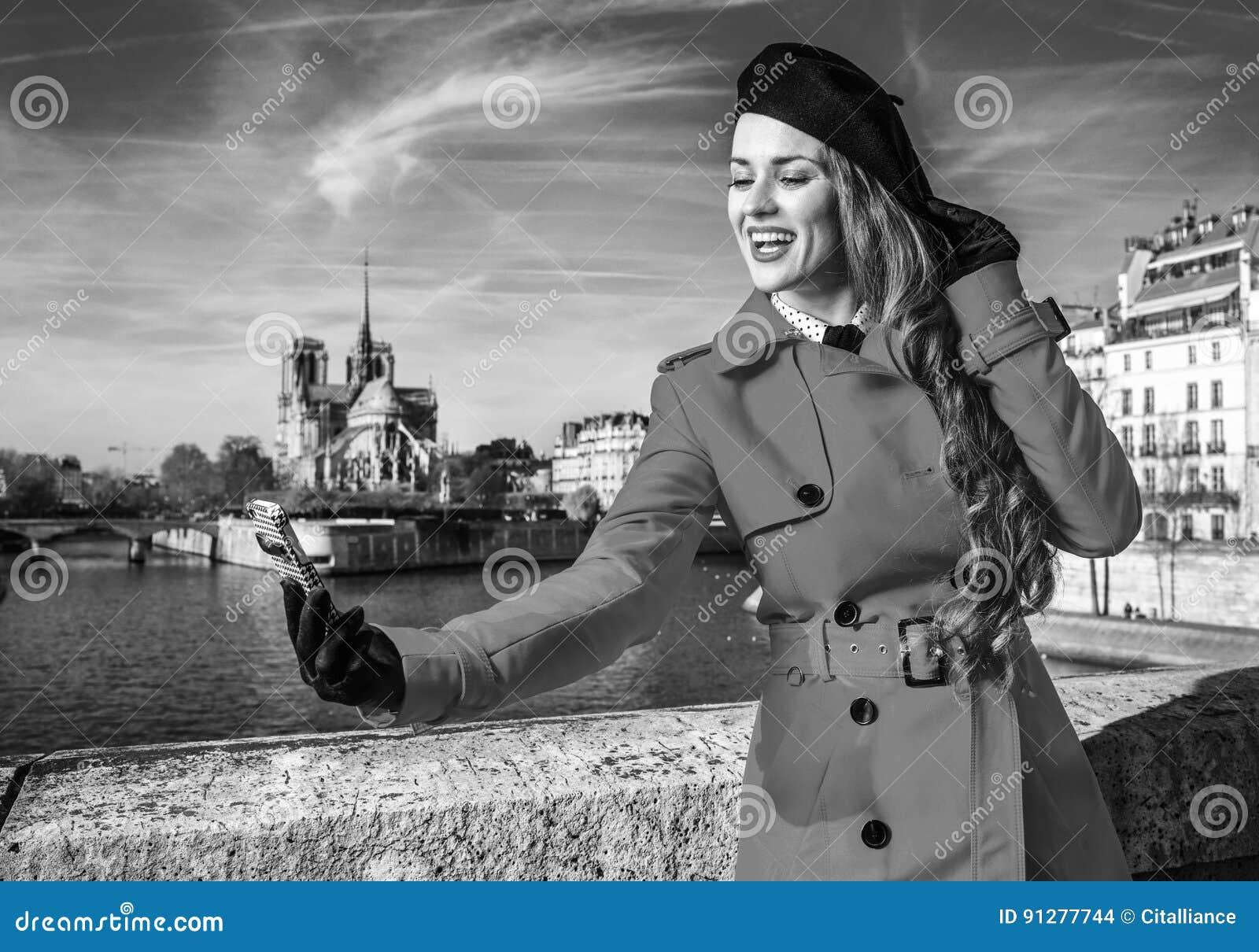 Kvinna på invallning i Paris, Frankrike som tar selfie med telefonen