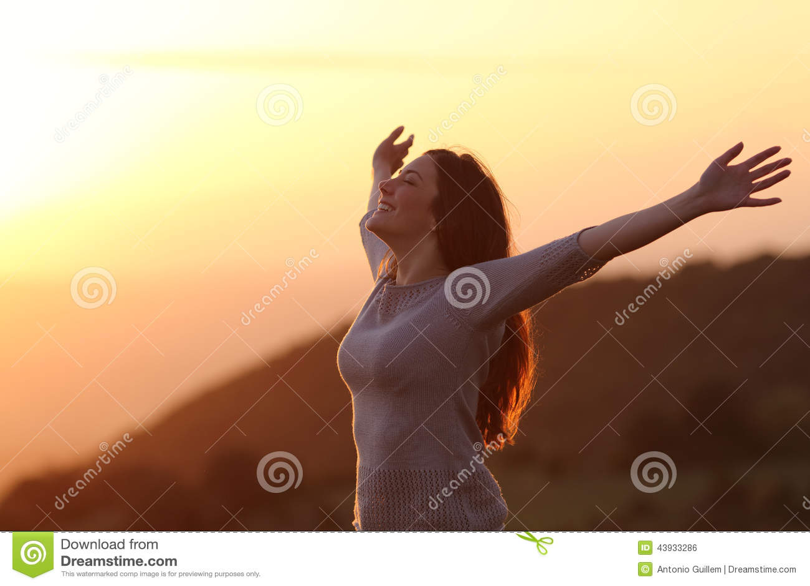 Kvinna på solnedgången som andas ny luft som lyfter armar