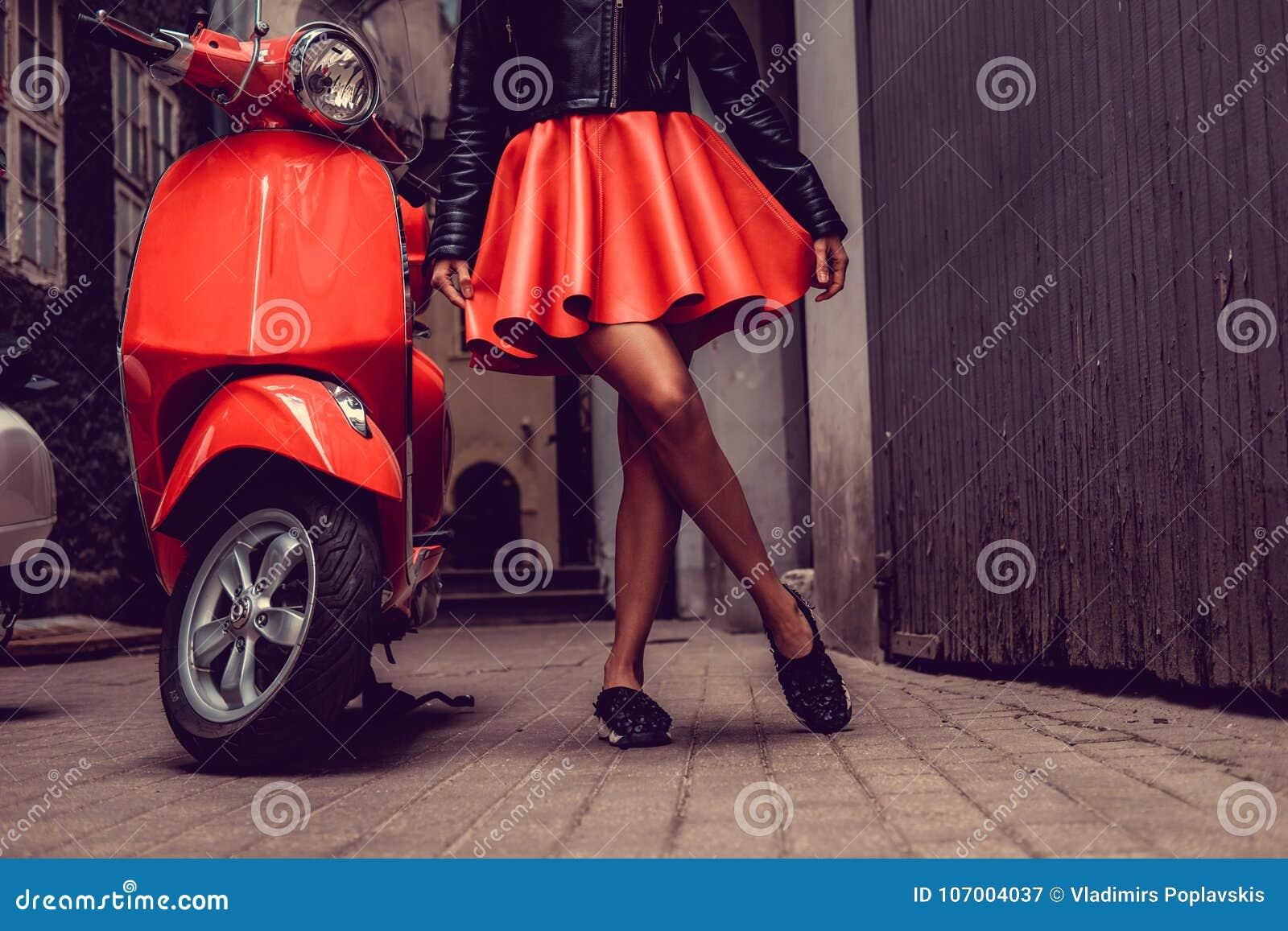 Kvinna` s lägger benen på ryggen nära den röda motoriska sparkcykeln