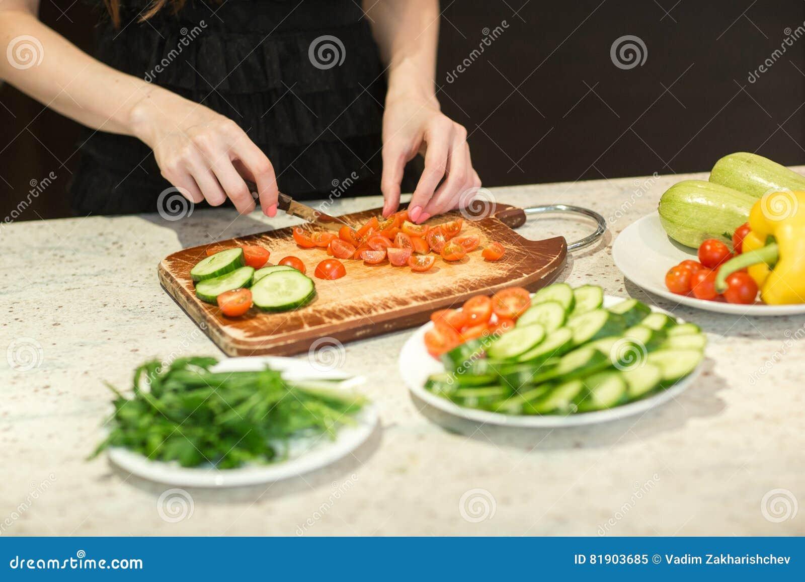 Kvinna` s räcker bitande grönsaker