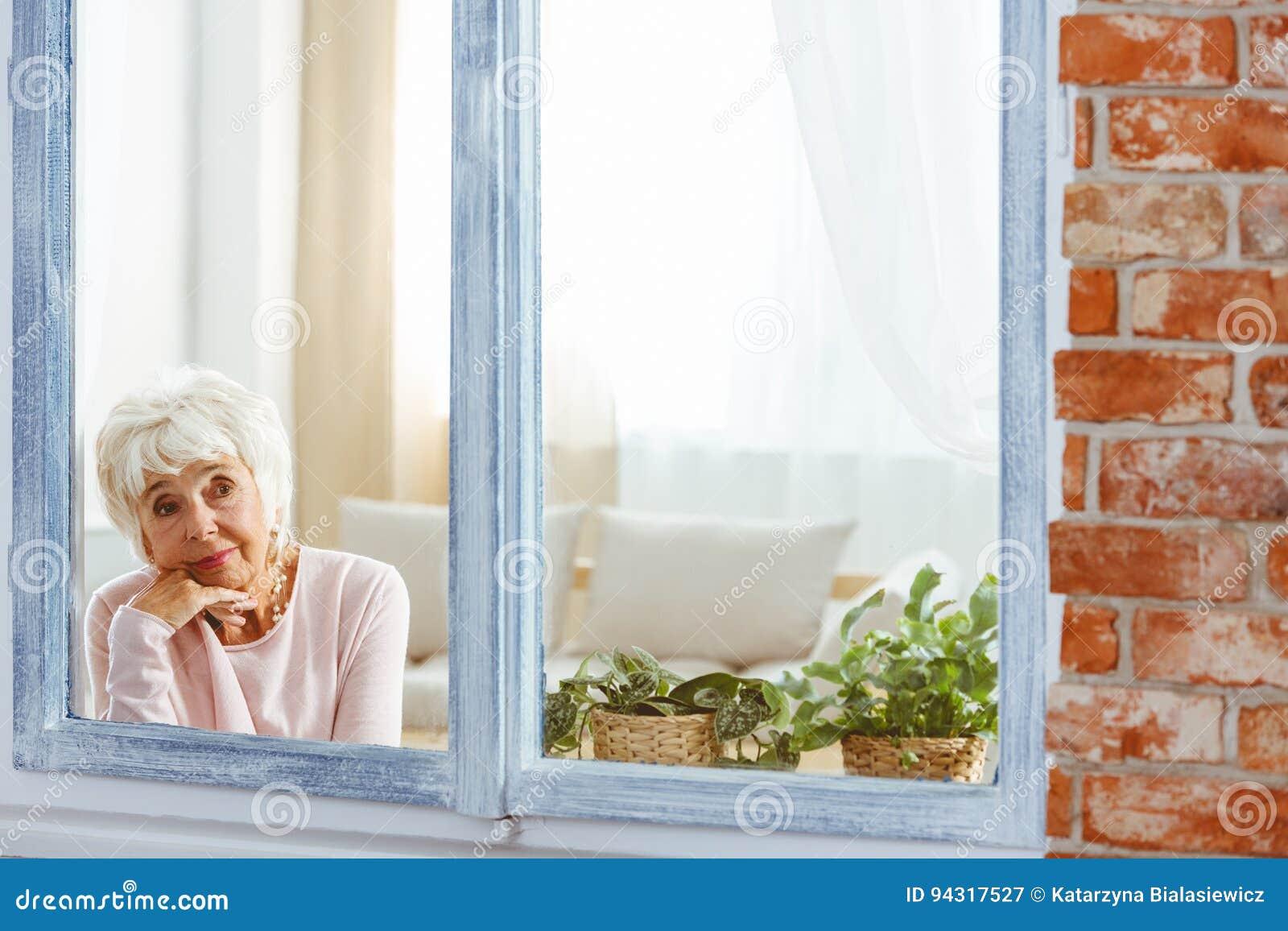 Kvinna som är borttappad i tanke vid fönstret