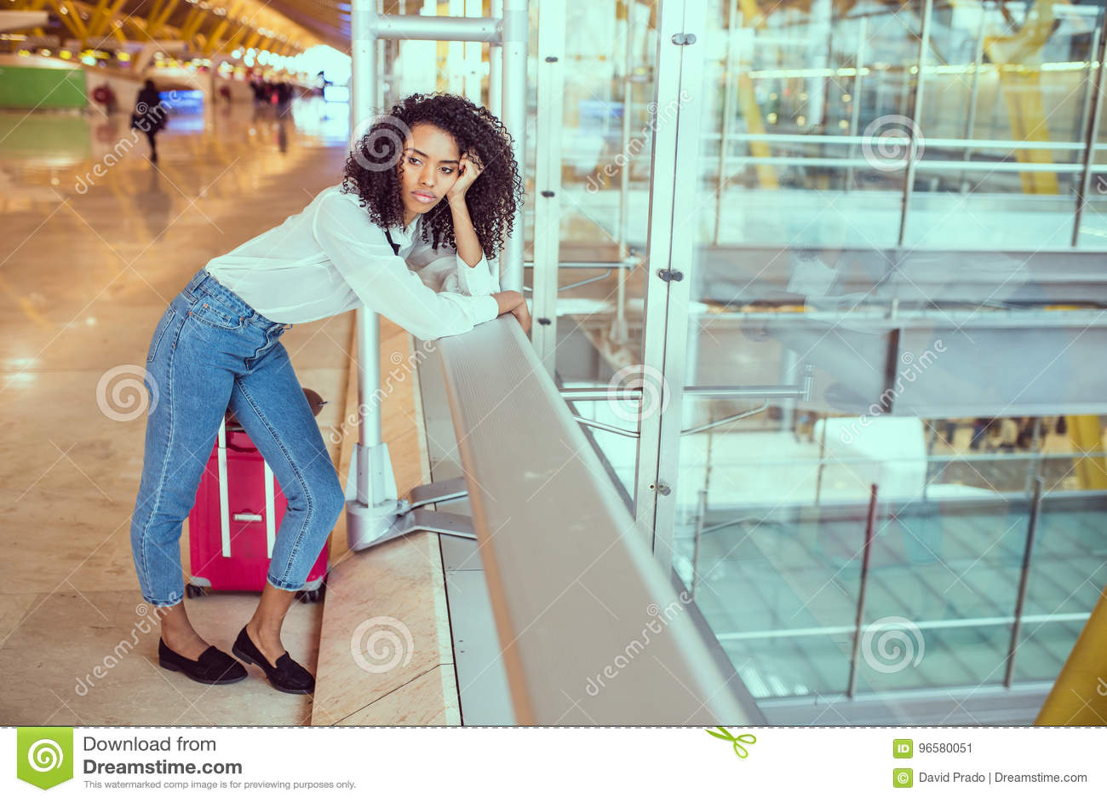 Kvinna som är ledsen och som är olycklig på flygplatsen med det avbrutna flyget