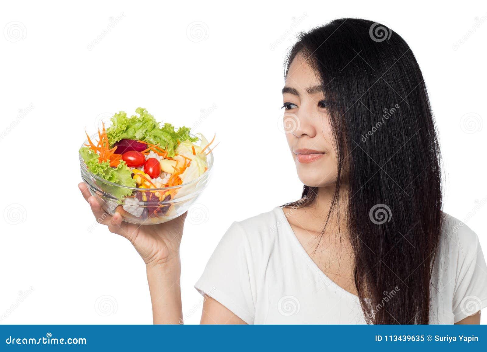 Kvinna som äter grönsaksallad som isoleras på vit