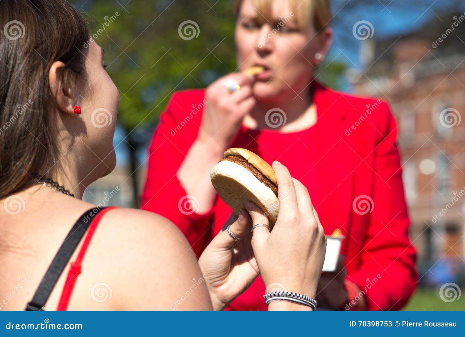 Kvinna som äter hamburgaren och pommes frites