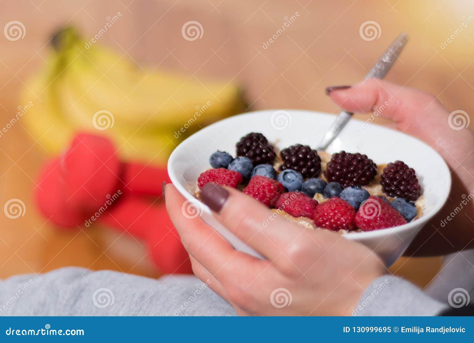 Kvinna som äter havrehavregröt i bunken som dekoreras med björnbär, hallon och blåbär