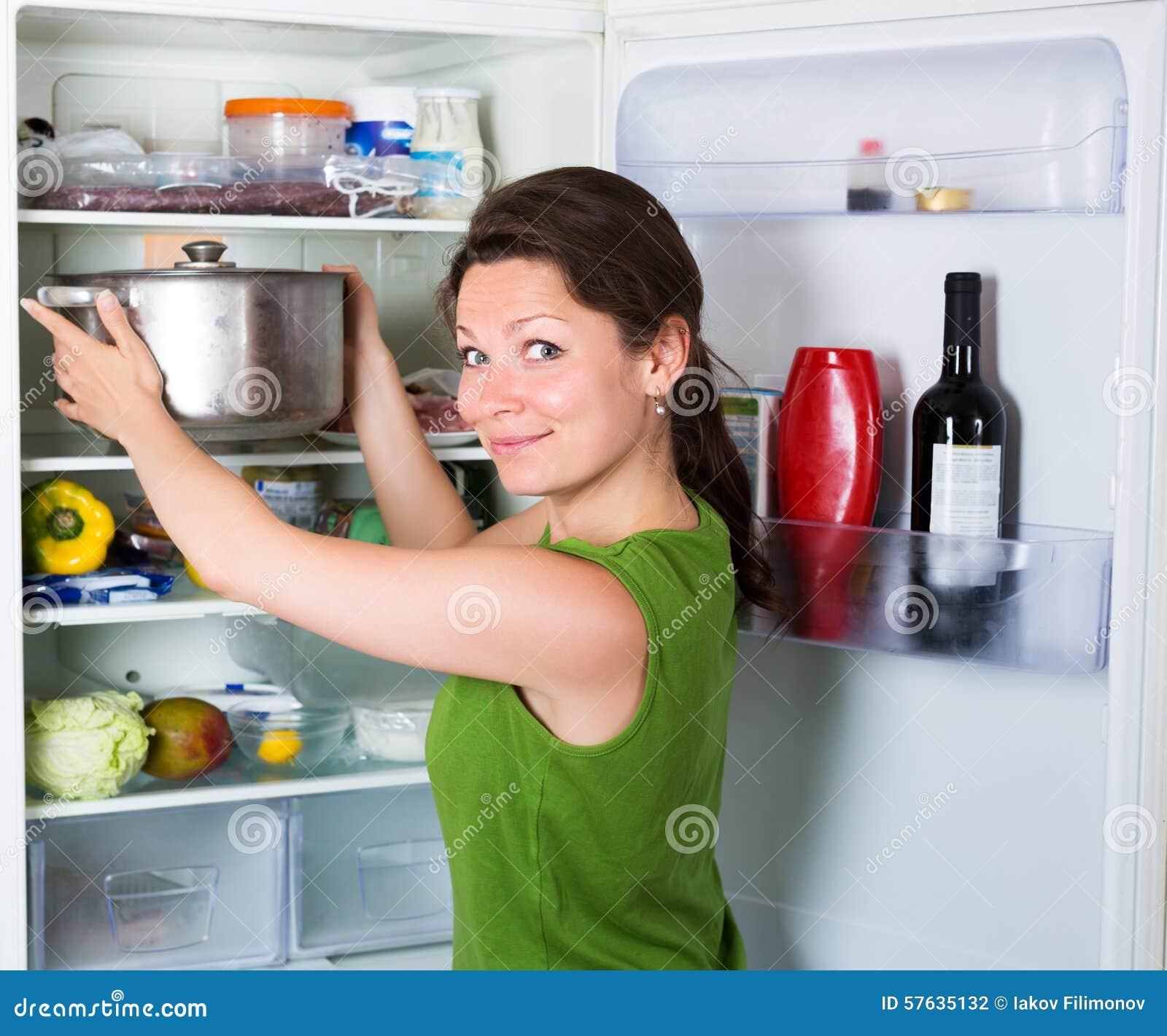 Kvinna som äter soppa från pannan