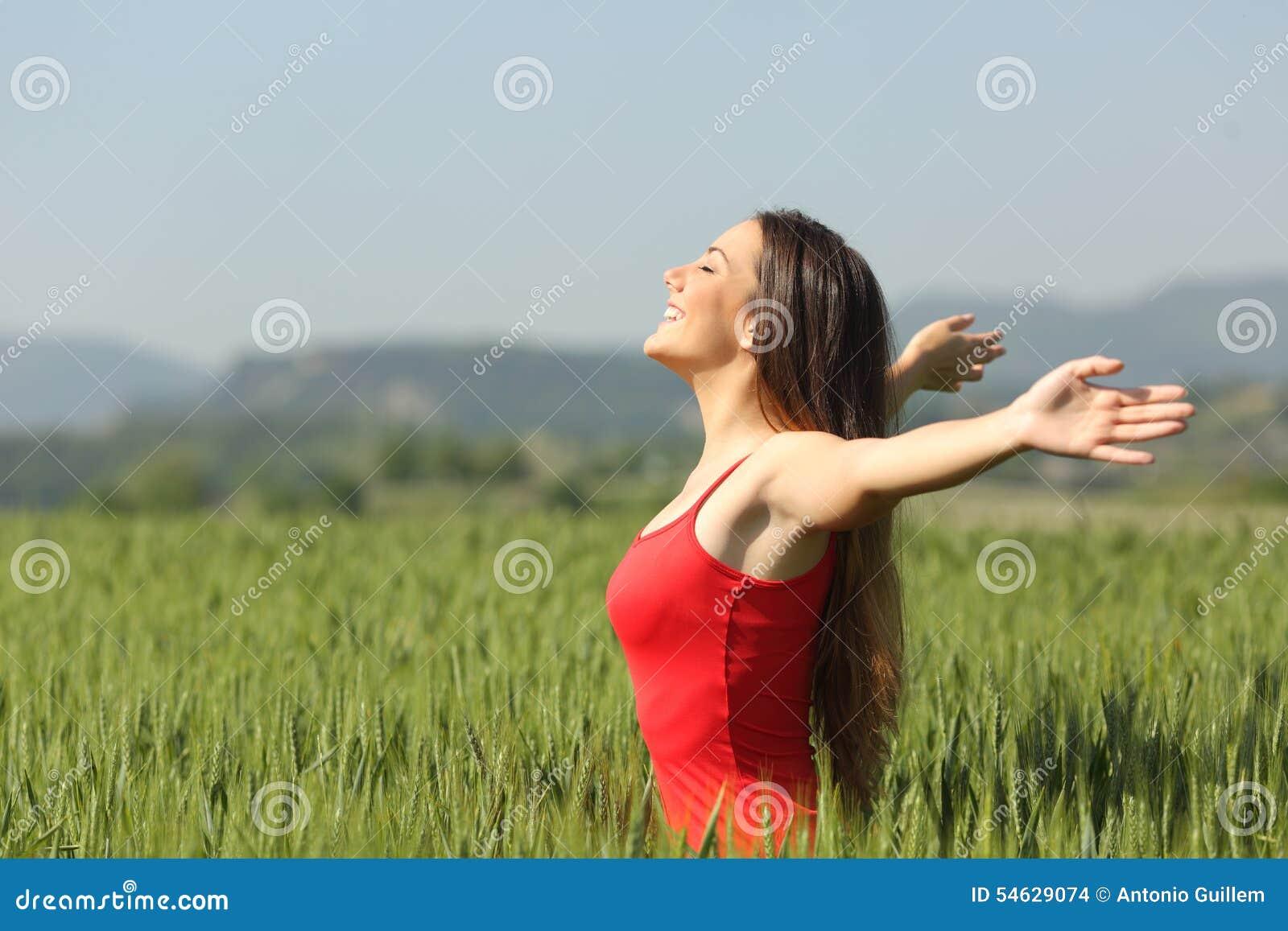 Kvinna som andas djup ny luft i ett fält