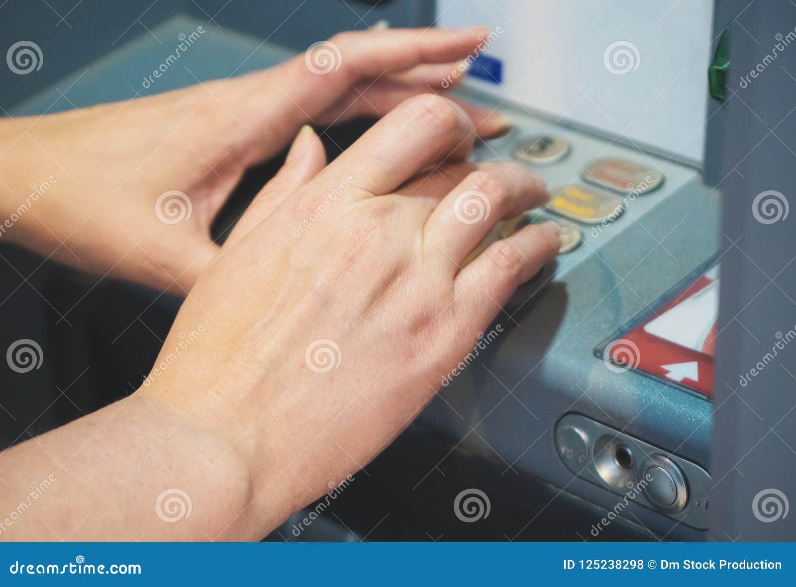 Kvinna som använder ATM på gatan