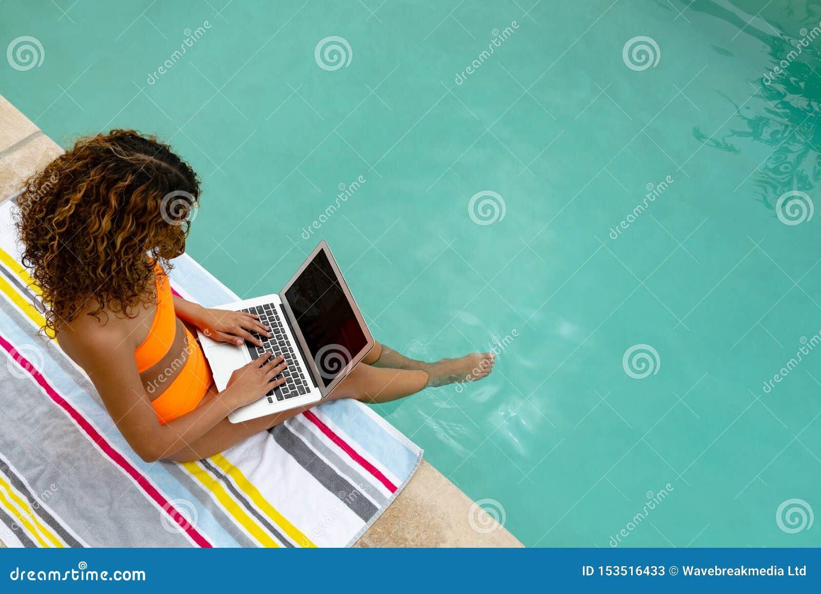 Kvinna som använder bärbara datorn, medan sitta på kanten av simbassängen