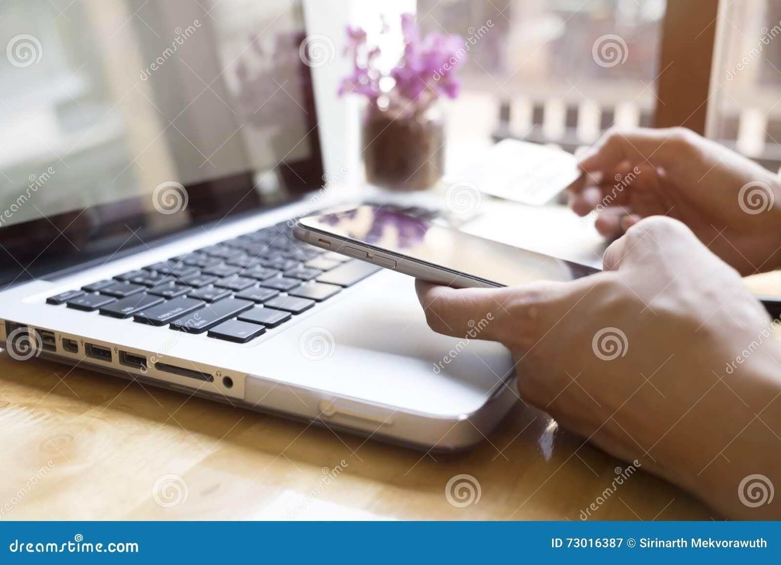 Kvinna som använder bärbara datorn och mobiltelefonen till online-shopping och lön vid kreditkorten
