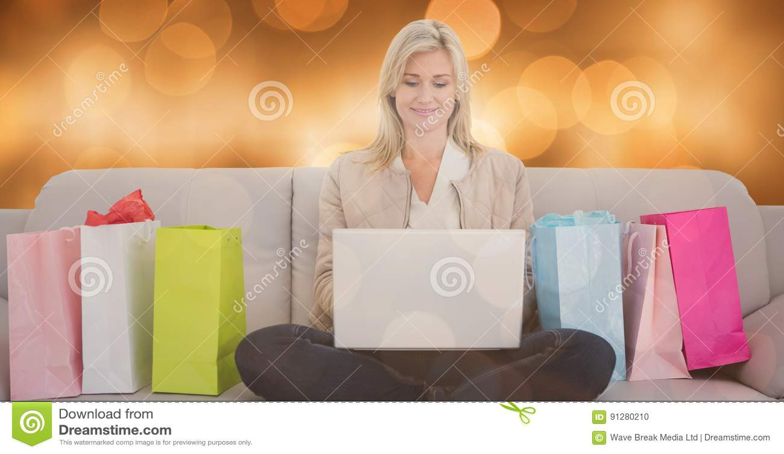 Kvinna som använder bärbara datorn vid shoppingpåsar på soffan över bokeh