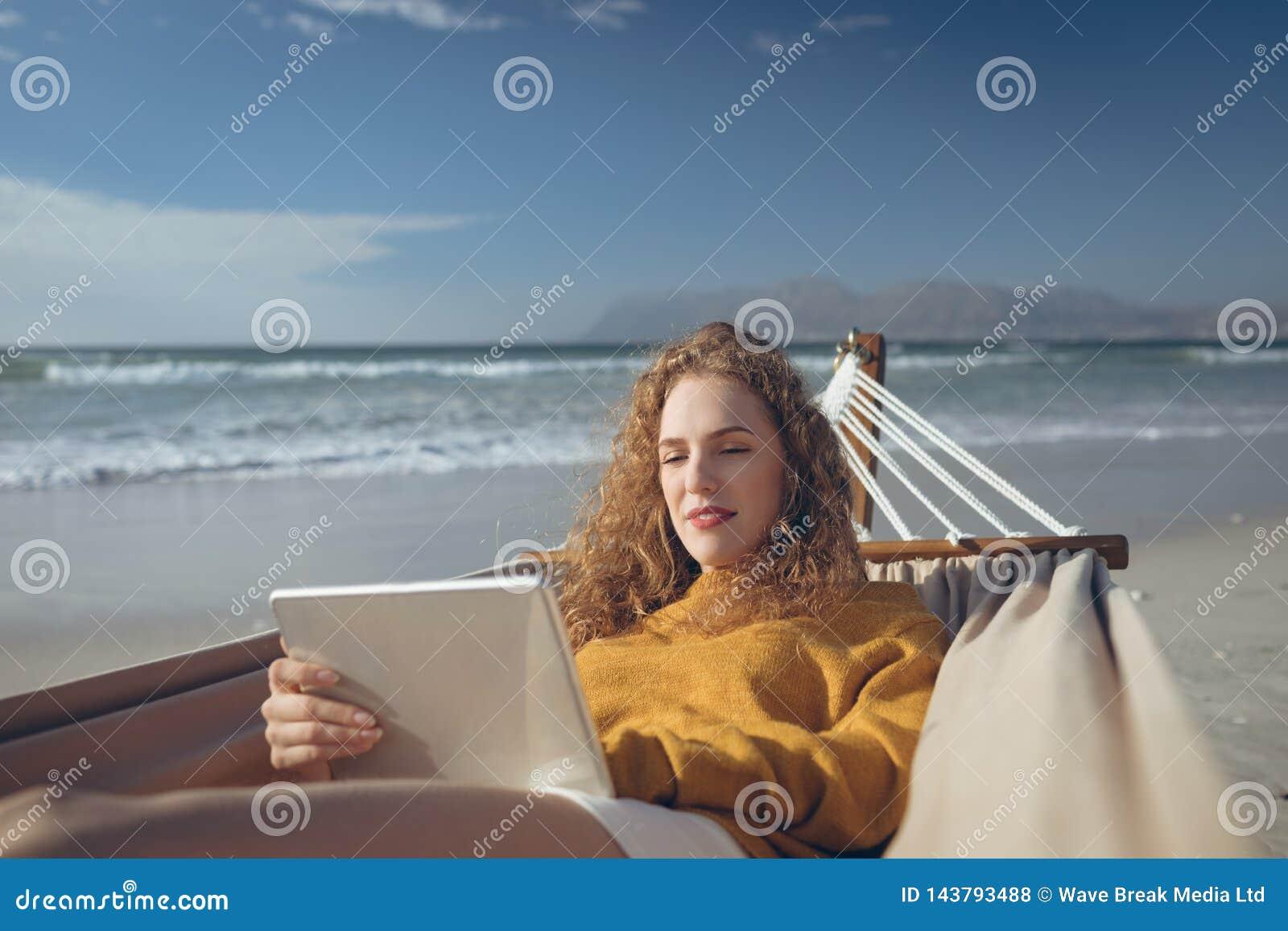 Kvinna som använder den digitala minnestavlan, medan ligga på hängmattan på stranden