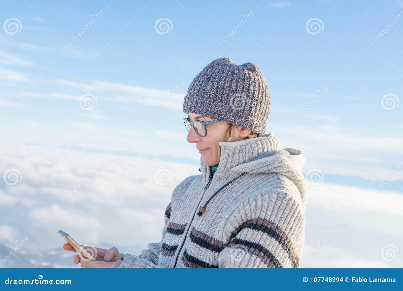 Kvinna som använder den smarta telefonen på bergen Panoramautsikt av snowcapped fjällängar i kall vintersäsong Begrepp av att del
