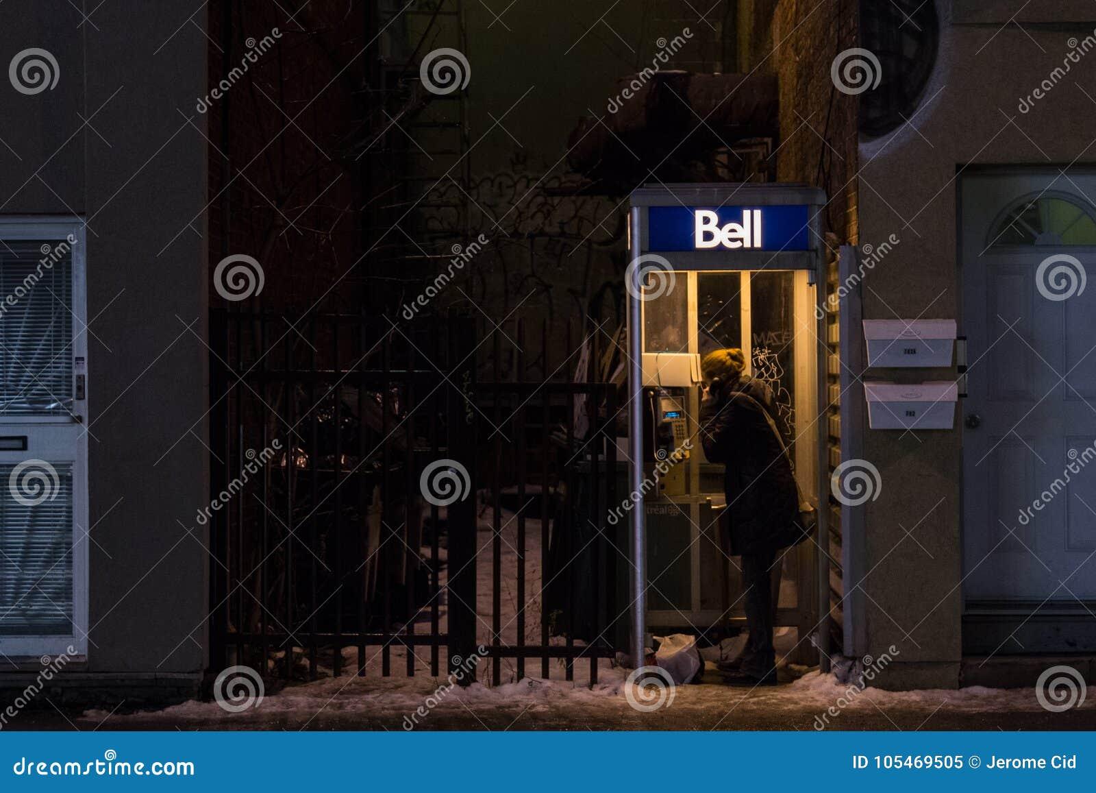Kvinna som använder en Bell Canada Payphone i Montreal i aftonen under tung snö