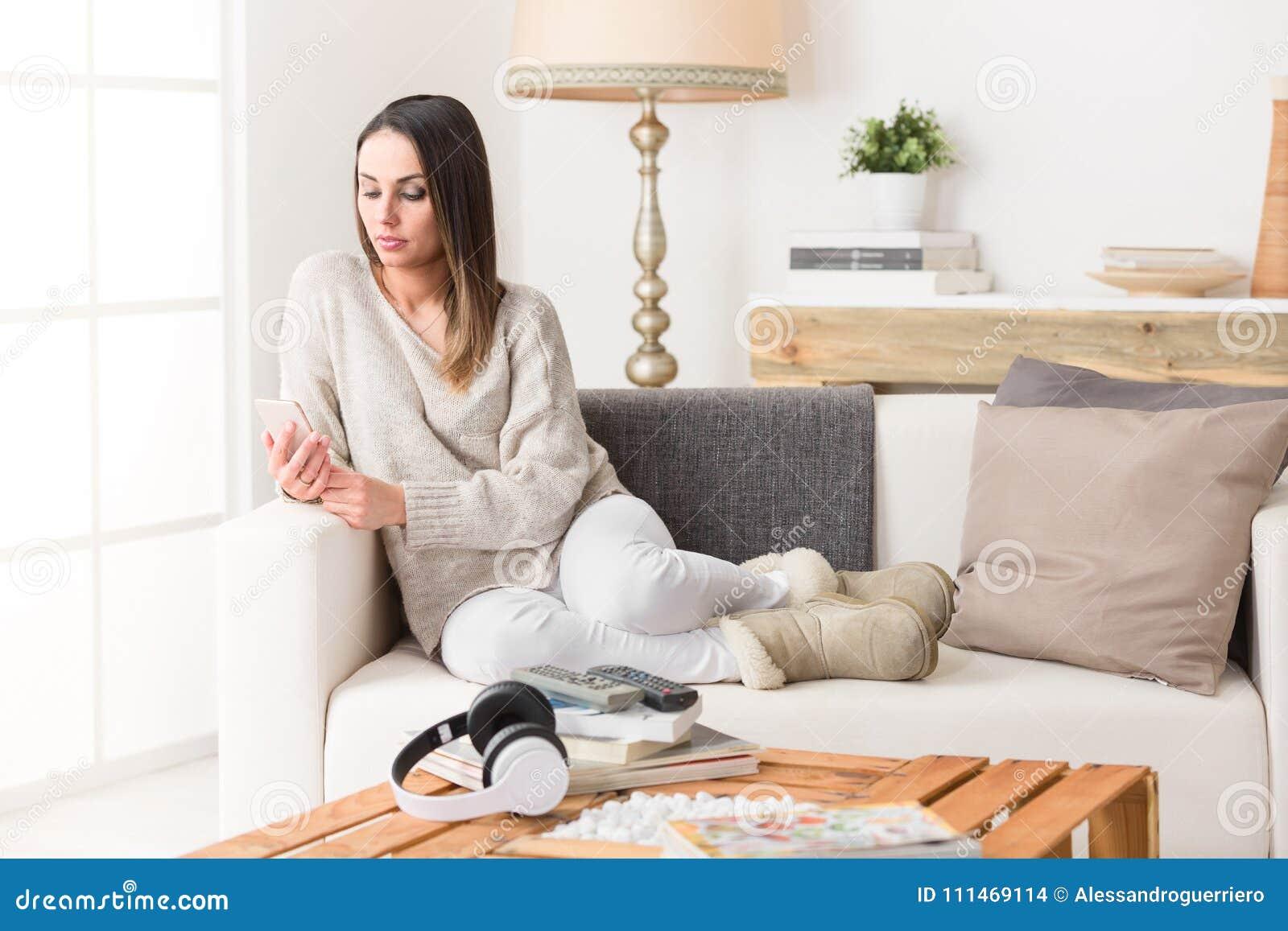 Kvinna som använder en smart telefon på en soffa
