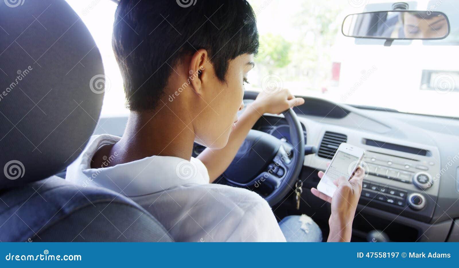Kvinna som använder mobiltelefonen, medan parkerat i bil
