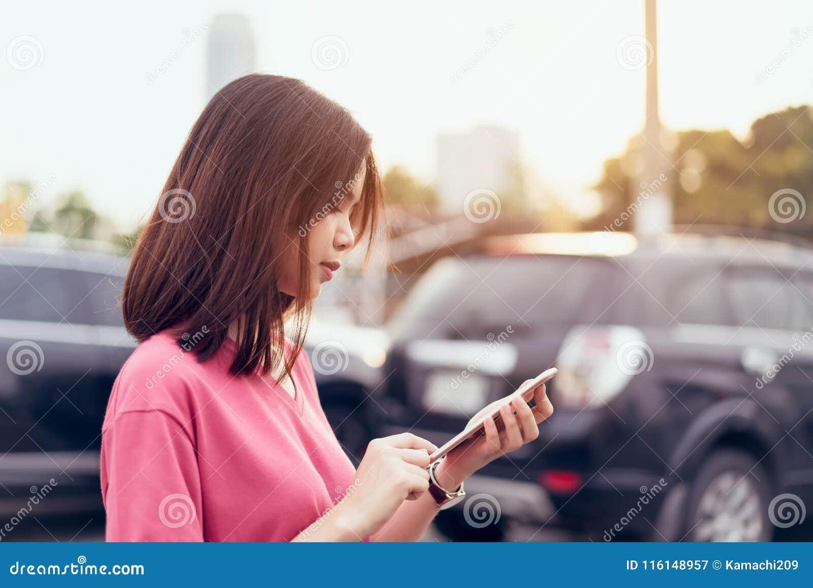 Kvinna som använder smartphonen för applikationen på bilsuddighetsbakgrund