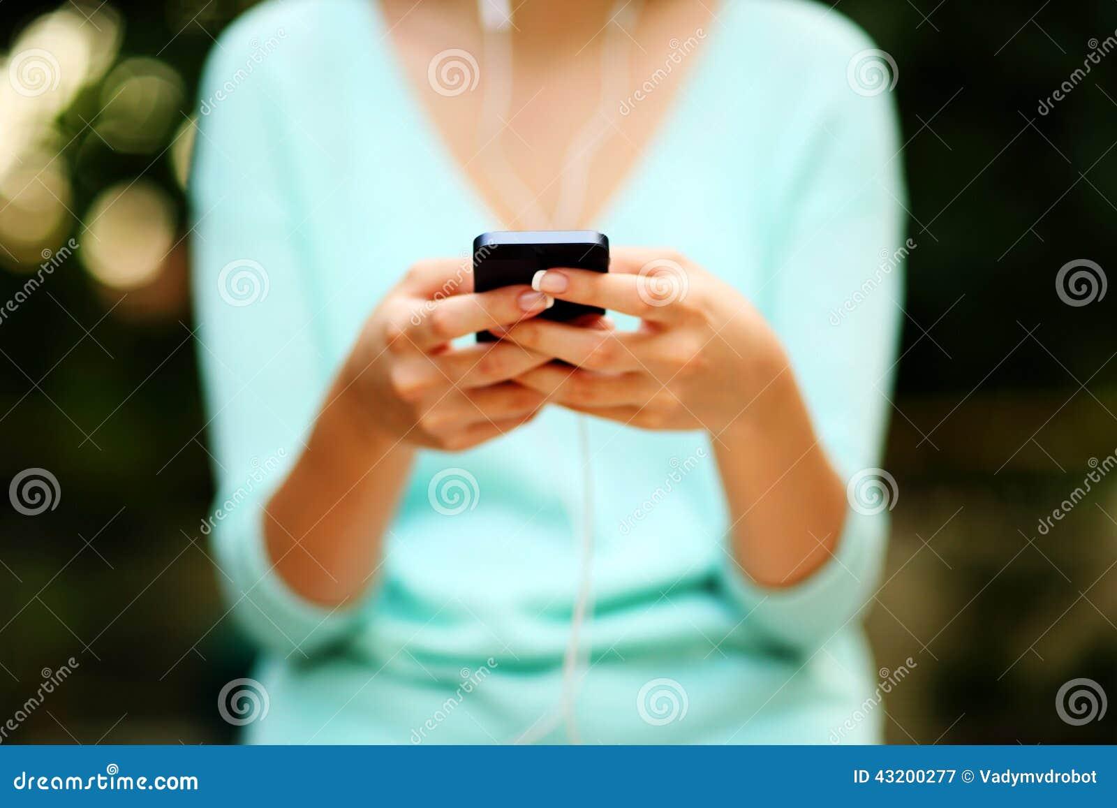 Download Kvinna Som Använder Smartphonen Med Hörlurar Fotografering för Bildbyråer - Bild av holding, armhåla: 43200277