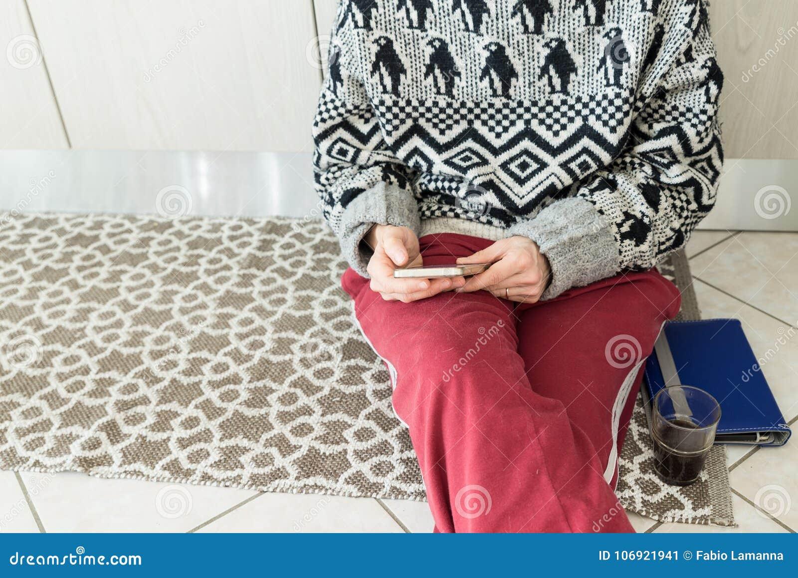 Kvinna som använder telefonen i hemmiljösammanträde på golv med minnestavla- och kaffeexponeringsglas Kroppsdel endast