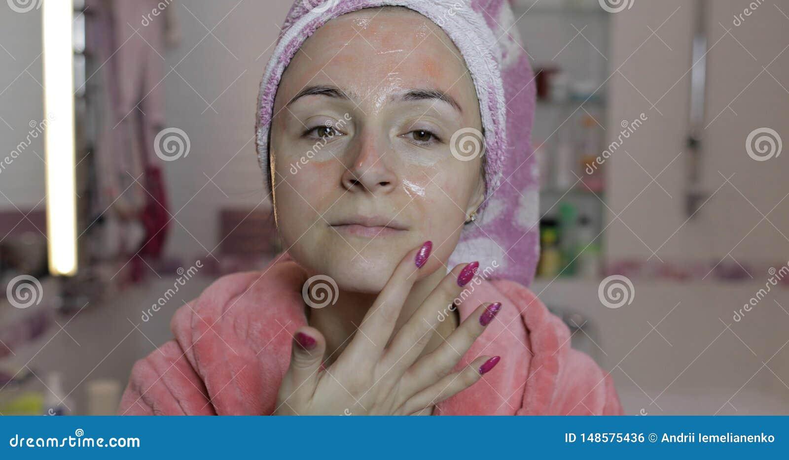 Kvinna som applicerar maskeringen som fuktar hudkr?m Skincare brunnsort Ansikts- maskering