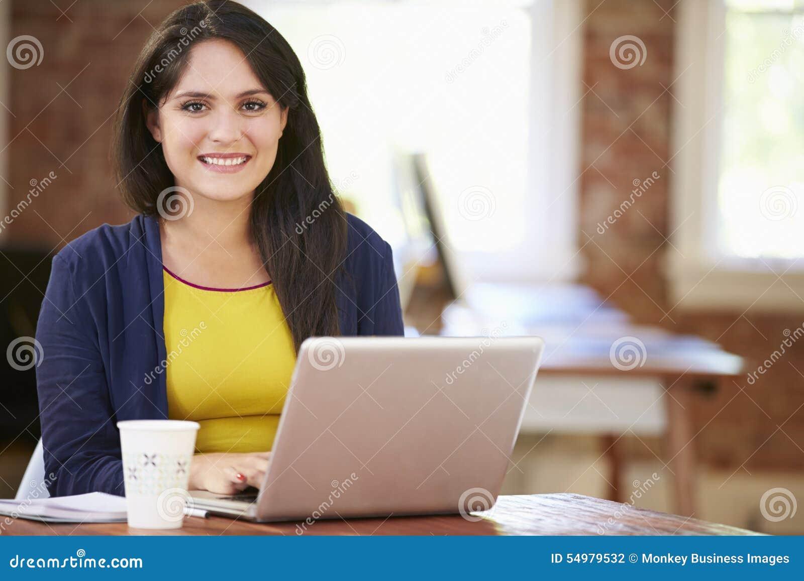 Kvinna som arbetar på bärbara datorn i modernt kontor