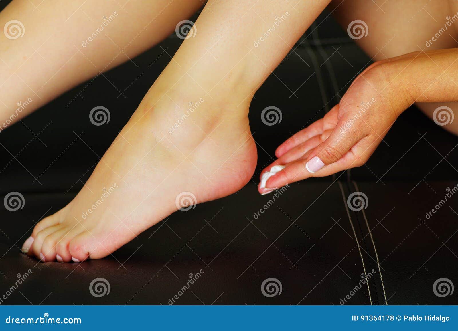 Kvinna som att bry sig om hennes fot och sätter hydratisera kräm på den