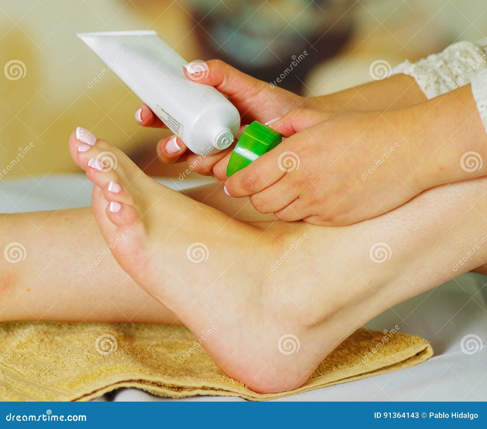 Kvinna som att bry sig om hennes fot och sätter hydratisera kräm på den med den kräm- flaskan