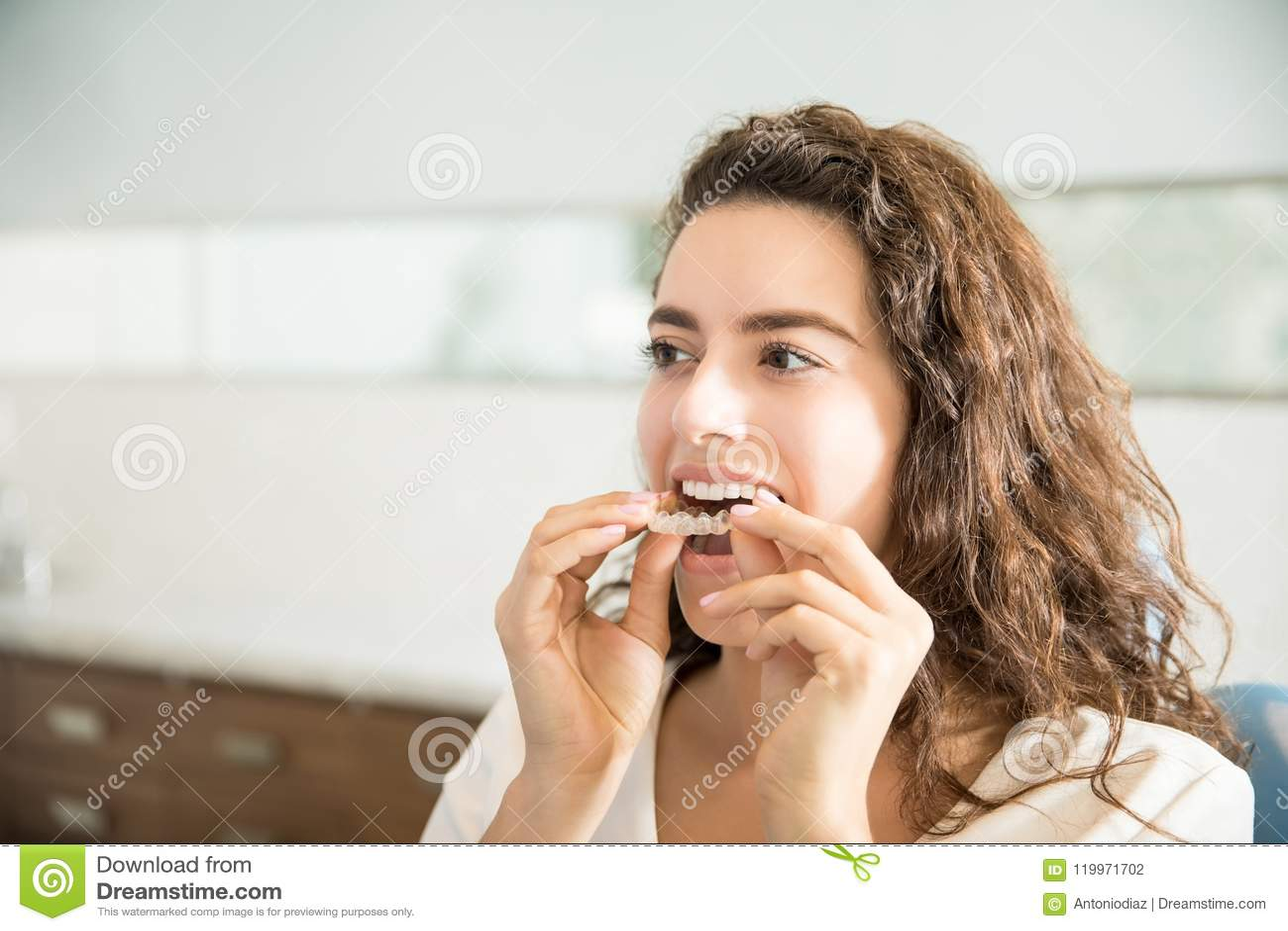 Kvinna som bär den klara tillrättaren i tand- klinik