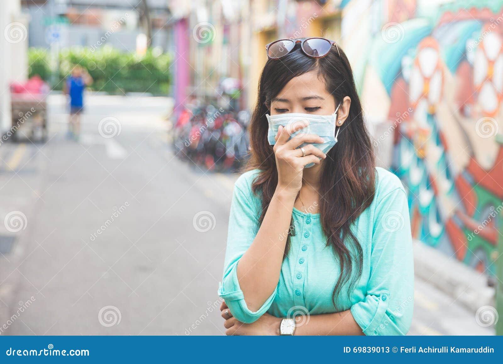 Kvinna som bär den medicinska framsidamaskeringen i stad