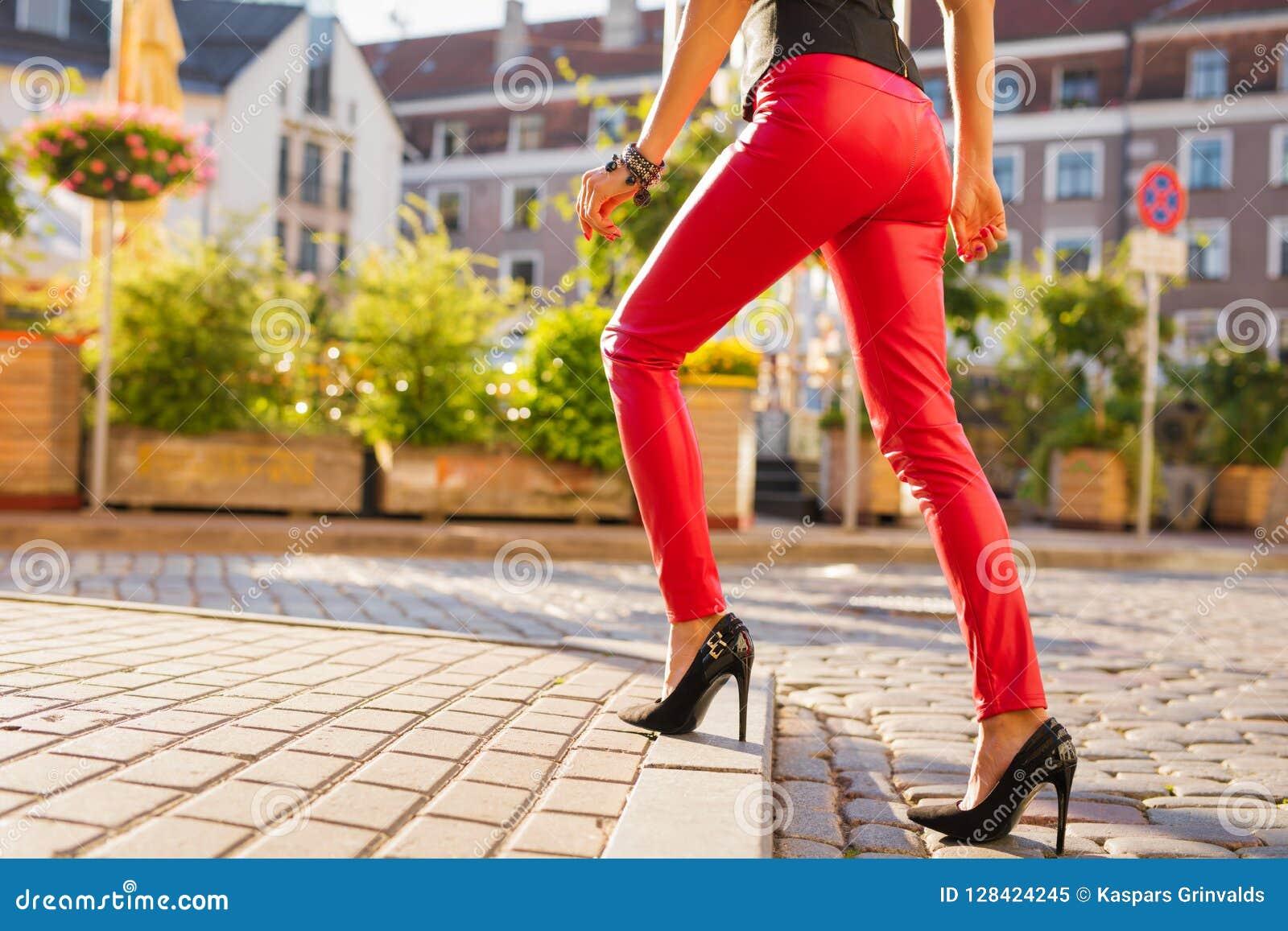Kvinna som bär röd läderbyxa och svarta skor för hög häl