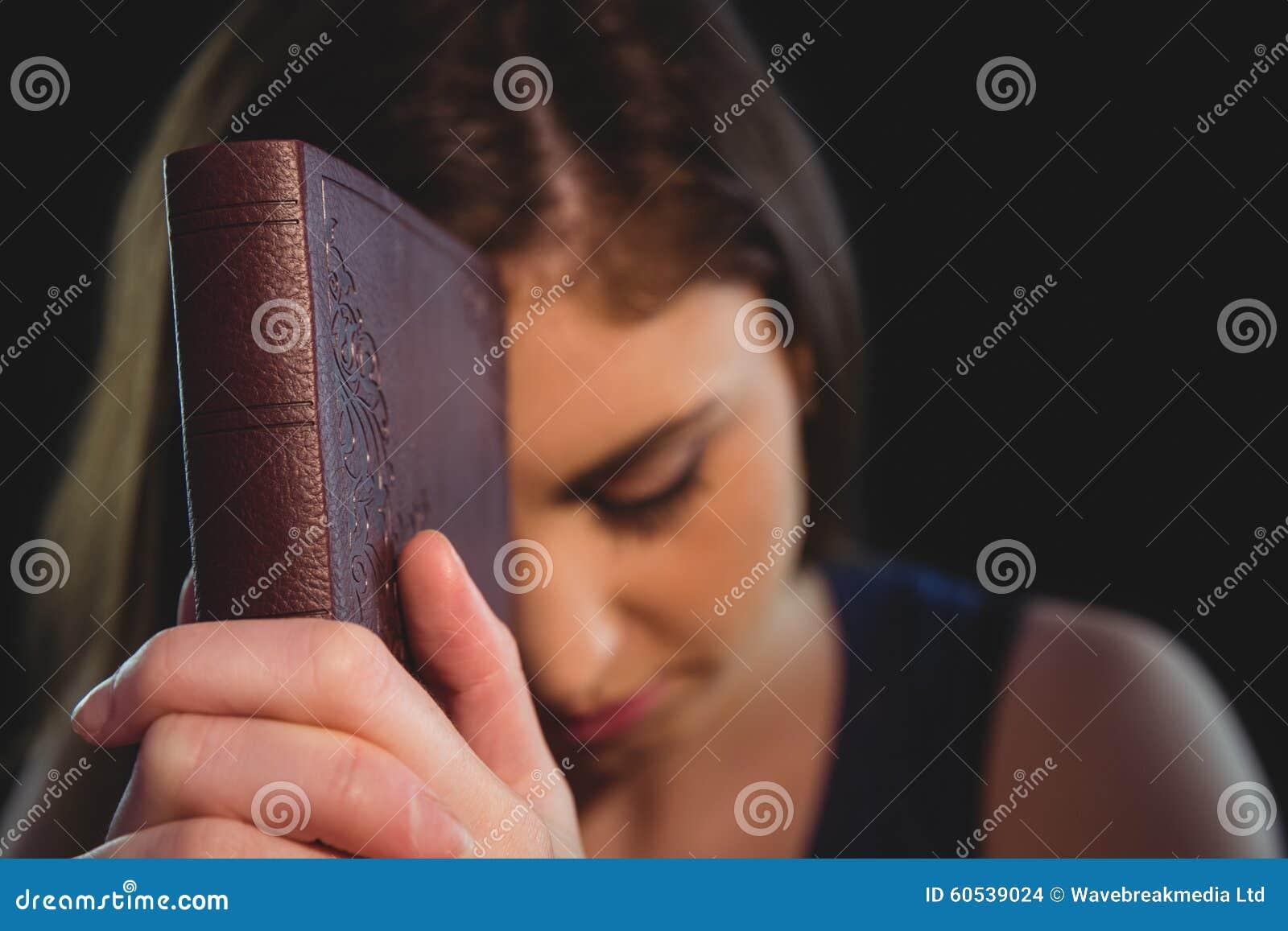 Kvinna som ber med hennes bibel
