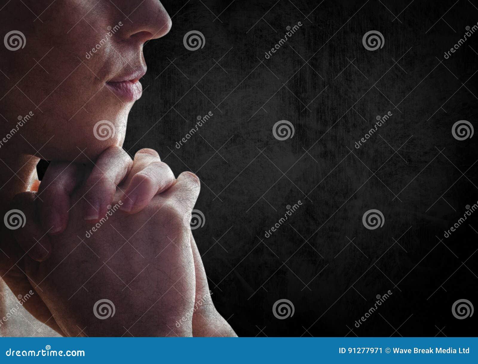 Kvinna som ber mot den svarta väggen