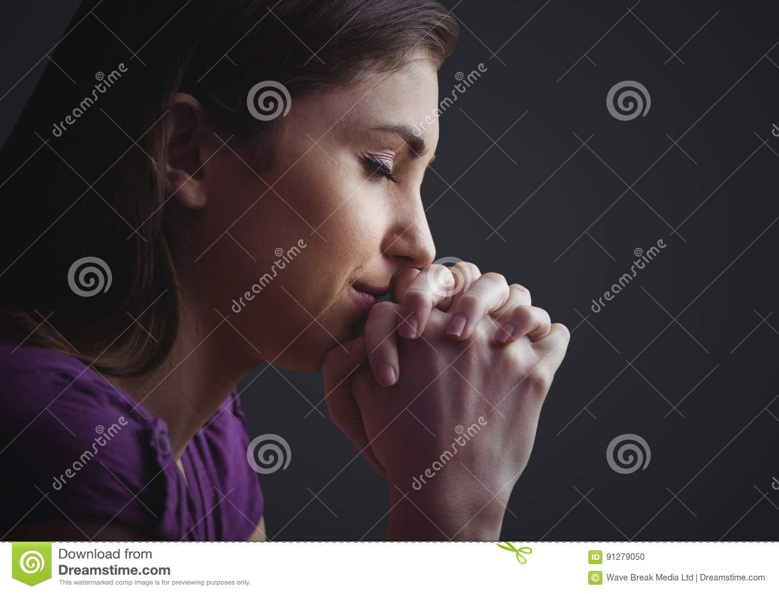 Kvinna som ber mot mörk grå bakgrund
