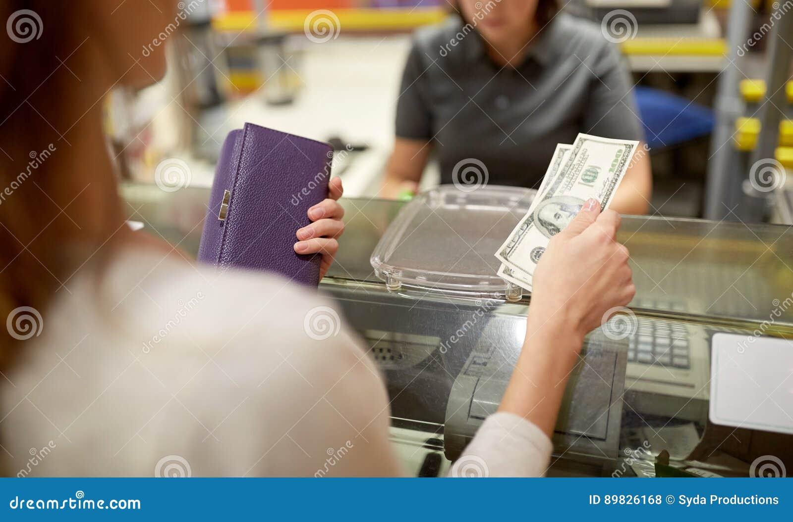 Kvinna som betalar pengar på lagerkassaapparaten