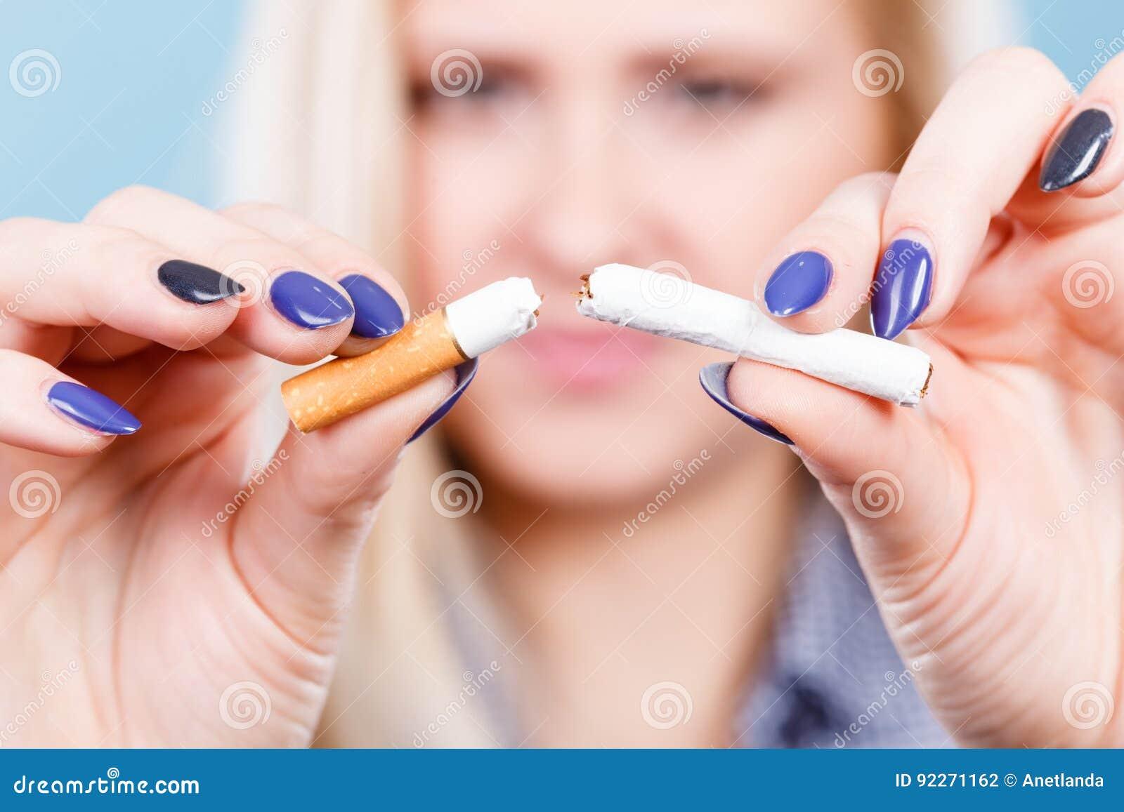Kvinna som bryter cigaretten som blir av med böjelse