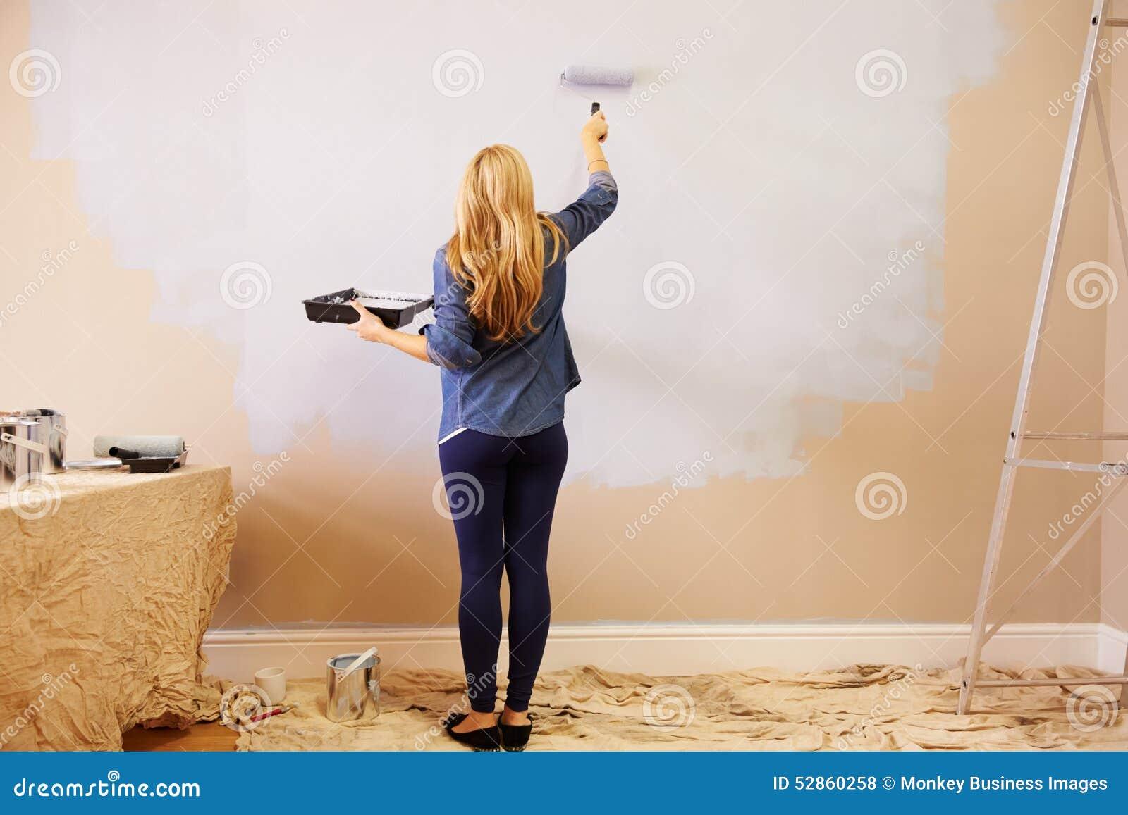 Kvinna som dekorerar rum genom att använda målarfärgrullen på väggen