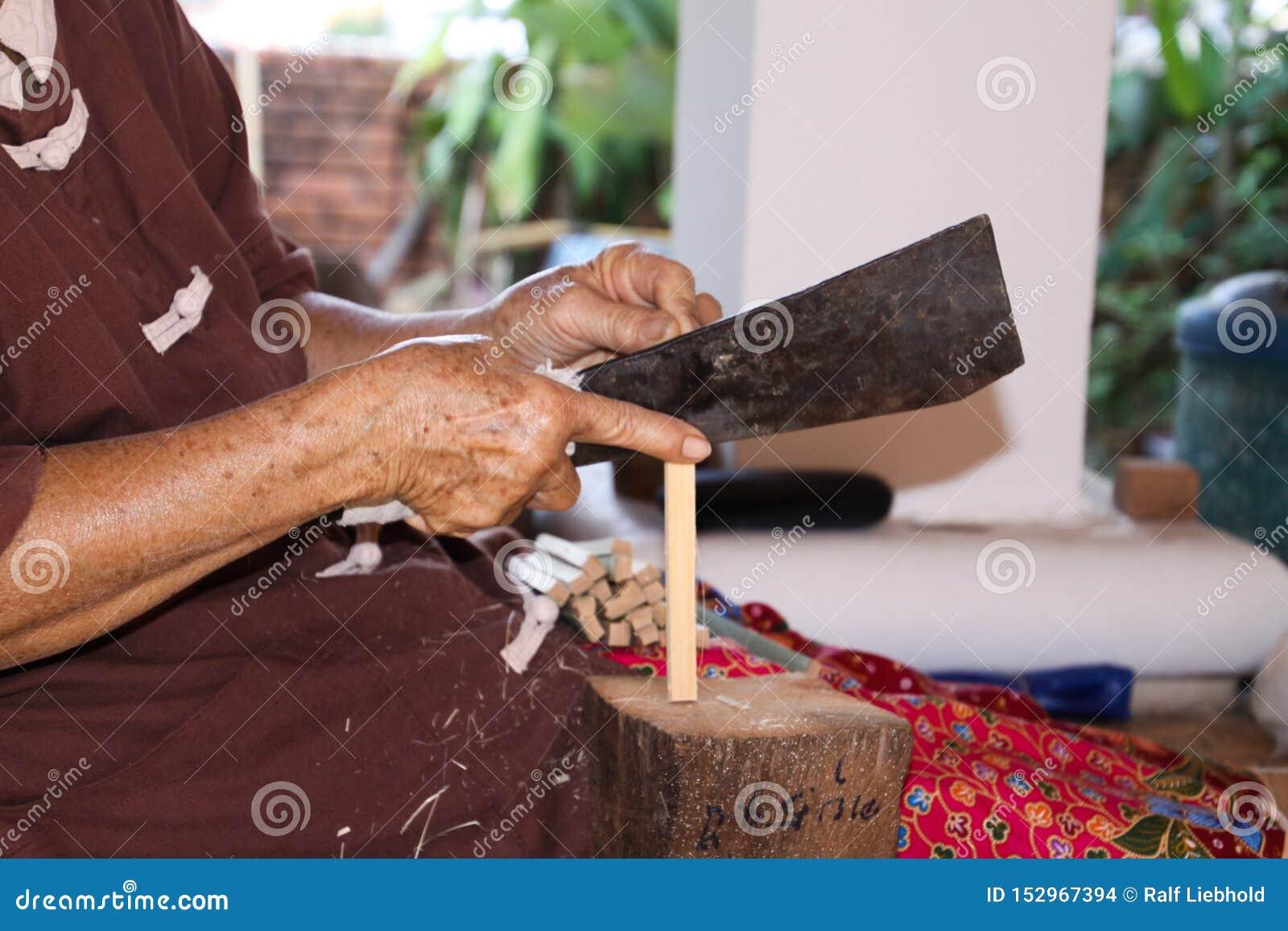 Kvinna som delar en pinne av bambuträ med en kniv i pappers- paraplyfabrik i Chiang Mai, Thailand