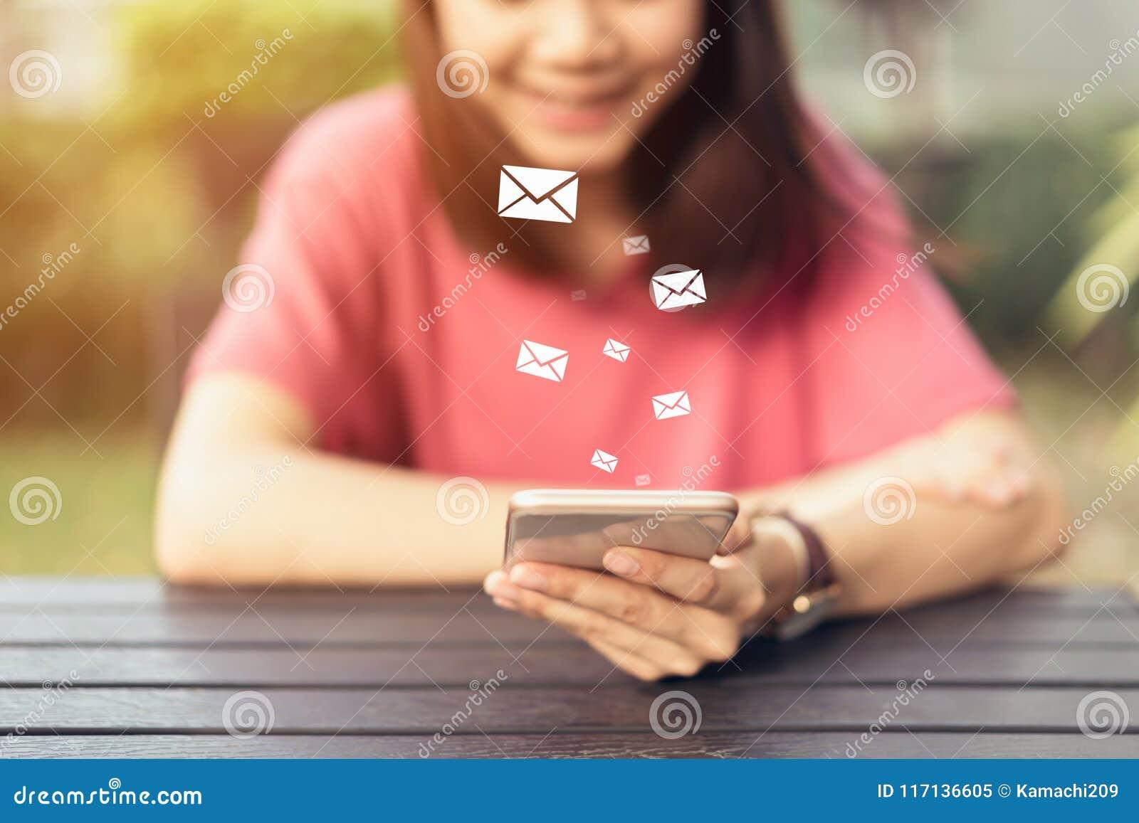 Kvinna som direktanslutet använder smartphonen och den sociala emailen för showsymbol, begrepp av kommunikationen och arbete