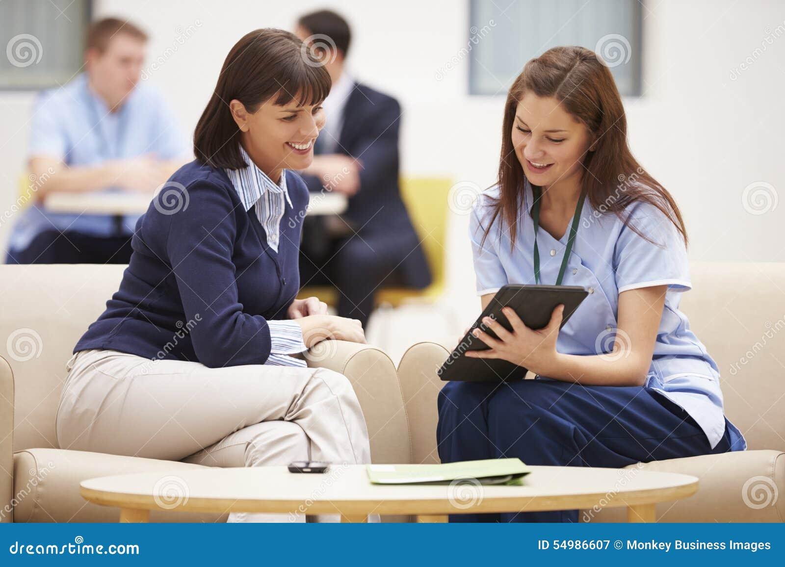 Kvinna som diskuterar resultat med sjuksköterskan On Digital Tablet