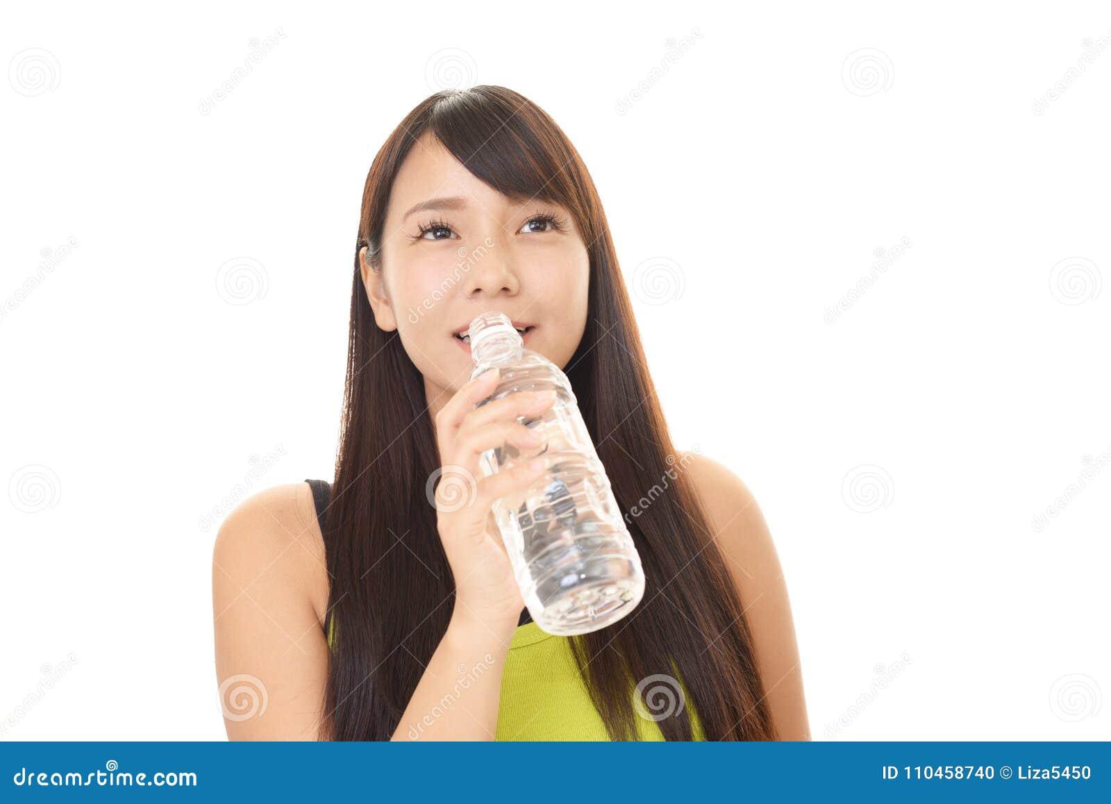 Kvinna som dricker en flaska av vatten