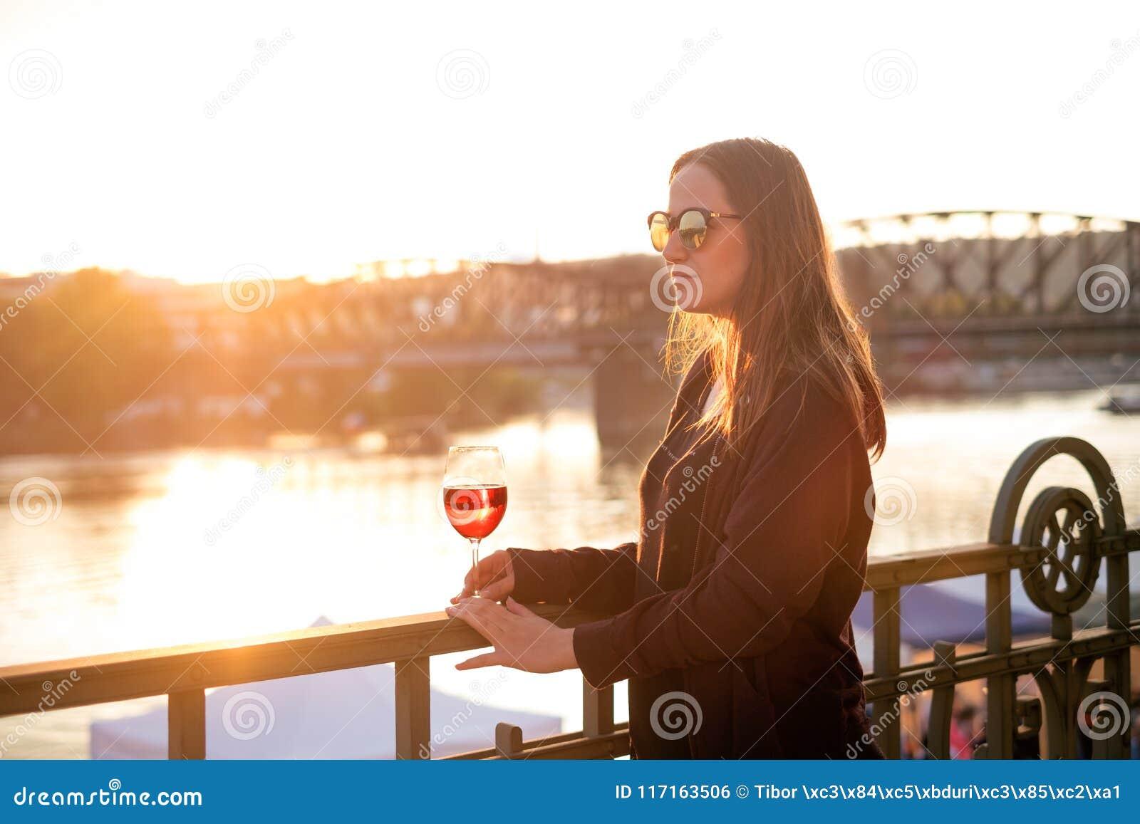 Kvinna som dricker ett vin i staden under en solnedgång glass rött vin Begrepp av fri tid i staden och drickaalkoholen